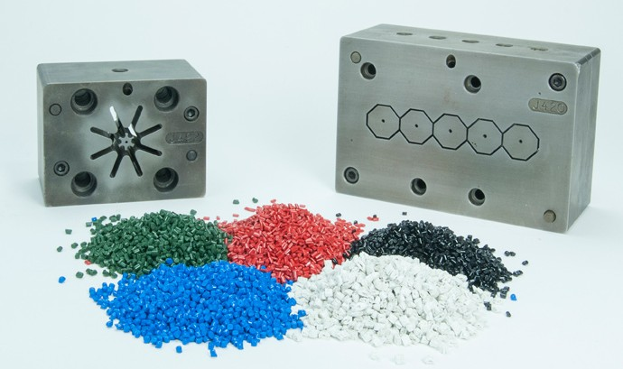 2 plastic extrusion molds behind green, red, blue, black, and white polymeric compounds