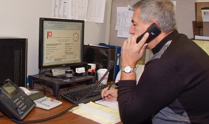 Man on the phone looking at Petro Extrusion website custom ordering